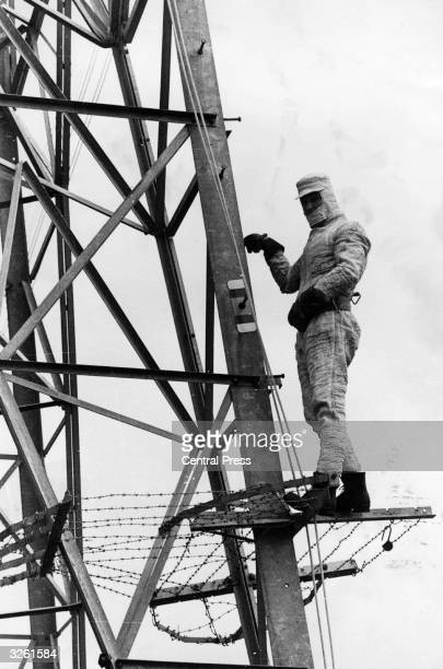 Linesman, working for the Central electricity generating board, wears a conductor suit and stands on an electricity pylon before being lowered onto a...