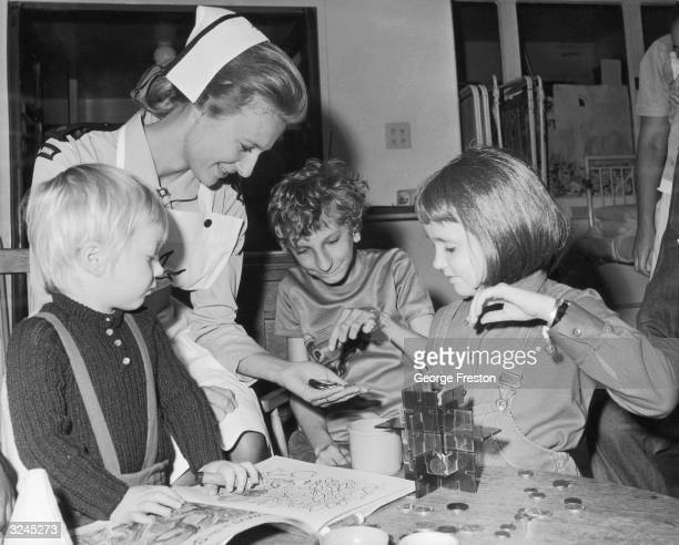 Princess Richard of Gloucester teaches three young patients at Great Ormond Street Children's Hospital to count money. She recently qualified in...
