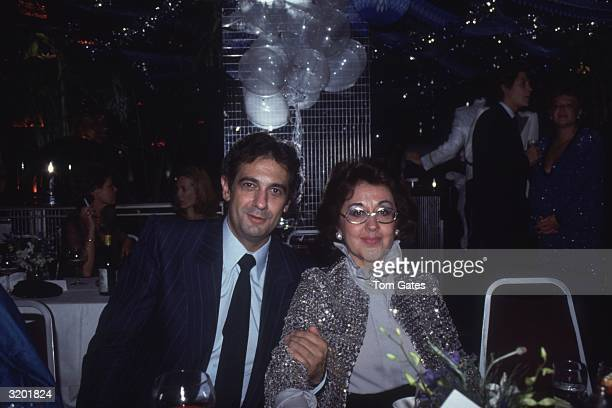 Spanish-born tenor Placido Domingo and his wife, Marta Ornelas, smile while seated at a party hosted by Arlene Dahl with the astrological sign Virgo...