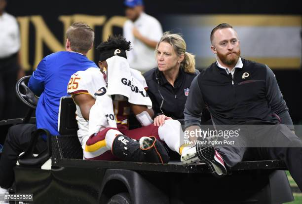 Washington Redskins running back Chris Thompson covers his face as he is carted off the field after suffering a leg injury during third quarter...