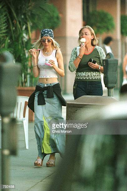 19yearold pop star Christina Aguilera pictured here looking very skinny and a unidentified person stroll Beverly Hills CA October 2 2000 while eating...
