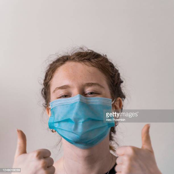 """19-years-old adolescent girl wearing a face mask looking into a camera and smiling behind the mask, demonstrating two """"thumb-up"""" signs with two hands. - 16 17 years stock pictures, royalty-free photos & images"""
