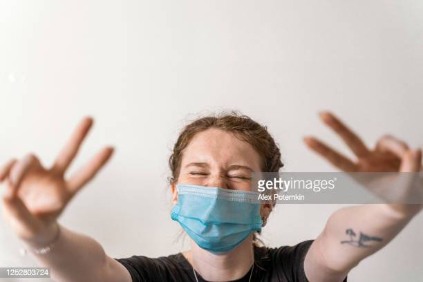 19-years-old adolescent girl wearing a face mask smiling behind the mask and showing a victory gesture toward the camera - 16 17 years stock pictures, royalty-free photos & images