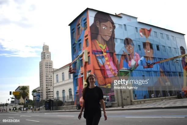 19yearsold graphic artist Luna Buschinelli poses in front of her mural that painted on the facade of the Rivadavia Correa Municipal School on...