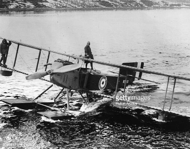 Men of the Royal Naval Air Service stand on top of a seaplane preparing to moor it during Allied intervention after the Russian Revolution on the...