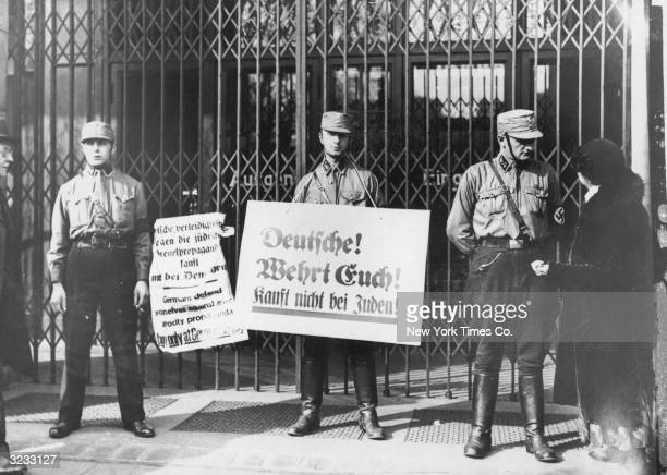 Nazi troops hold antiSemitic placards in front of a locked storefront in the organised boycott of German Jewish businesses Berlin Germany One of the...