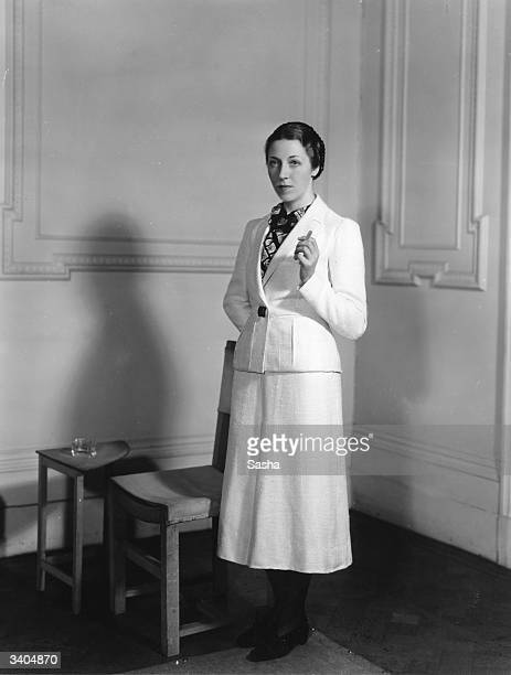 English aviator Amy Mollison nee Johnson wearing a woollen suit from the collection of flight clothes designed by Madame Schiaparelli for her solo...