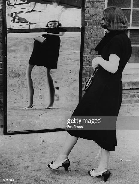 Woman gets a kick out of a novelty mirror at Southend, showing her longer skirt as short.