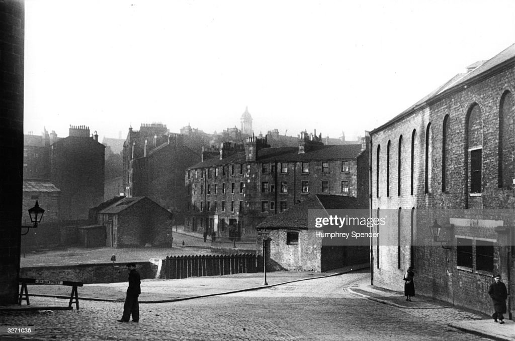 A poor area of Clydeside. Glasgow began an ambitious housing plan in 1919 when it was estimated that 57,000 new homes were needed including 21,000 to ease overcrowding and 15,000 for the expanding population. By May 1937 66,619 houses were built or being constructed with electric light and especially low rent for residents being rehoused. Original Publication: Picture Post - 91 - Clydeside In The 1930's - pub. 1939