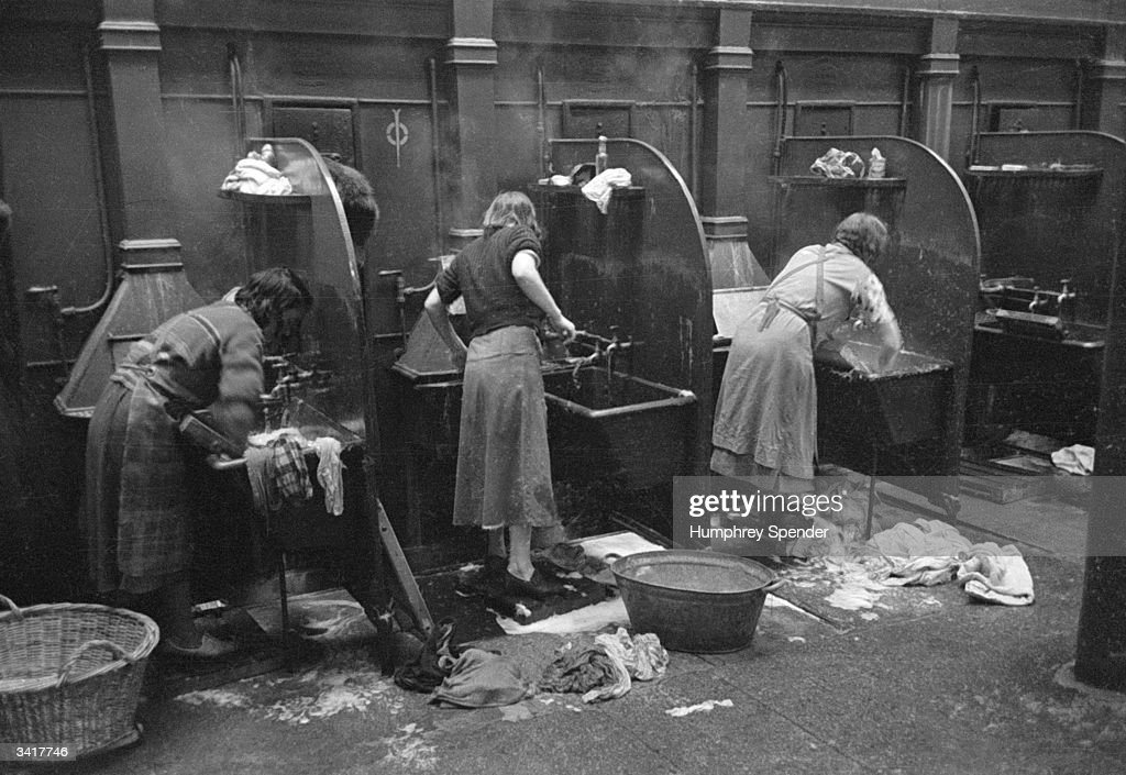 Glaswegian housewives doing their laundry at a municipal wash-house known as a 'steamie', which is connected to the public baths. Many of Glasgow's residents live in one or two-room houses and so few people have the facilities or hot water to do their washing at home. Original Publication: Picture Post - 91 - Glasgow - pub. 1939