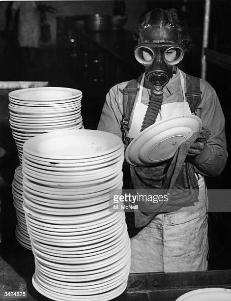 An ATS girl of the Eastern Command washing dishes while wearing her gas mask during a refresher course of antigas training