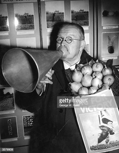Councillor AJ Blake, Chairman of the Wartime Allotments Committee holding a megaphone and a sack of onions before launching an allotment exhibition...