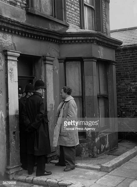 Policemen standing in the doorway of Number 10 Rillington Place London where serial killer John Reginald Christie lived and buried the bodies of his...