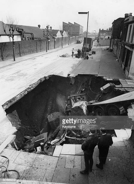 Bystanders look at a lorry which crashed into a large hole which suddenly appeared in Plumstead Road Woolwich