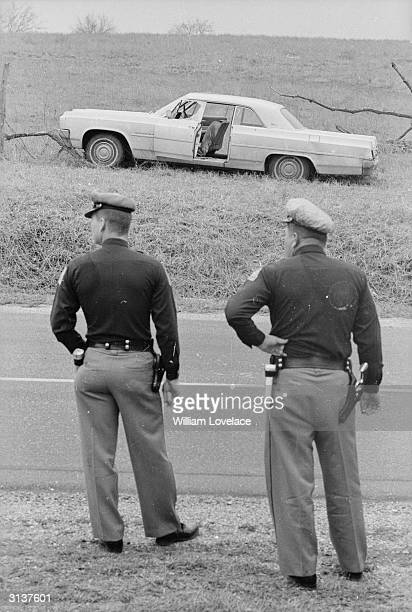 Two Alabama state troopers standing over the road from the wreck of the car belonging to the murdered Detroit housewife, Viola Liuzzo , who was...