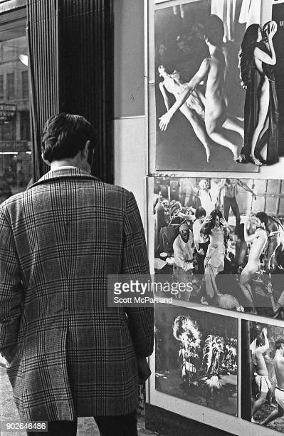 A man stops to look at a adult film advertisement under the marquee of one of the many adult movie theaters on 42nd street in Times Square New York