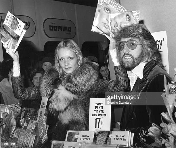 British fashion model Twiggy sells her own brand of tights in the hosiery department at Selfridges department store, London. Giving her a helping...