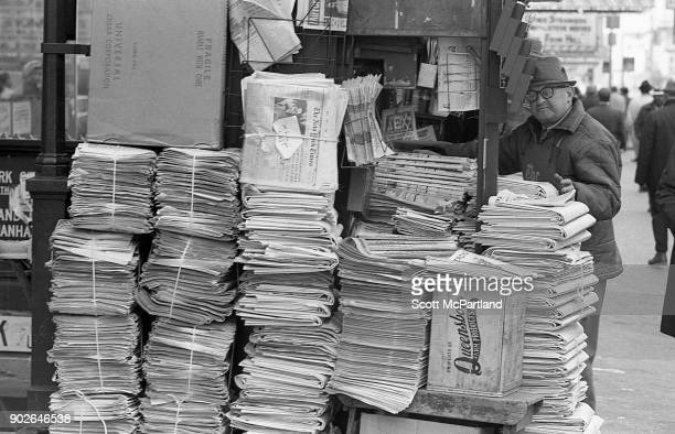 Stacks of New York Times newspapers sit next to a man's newsstand on 42nd street in Times Square, New York.