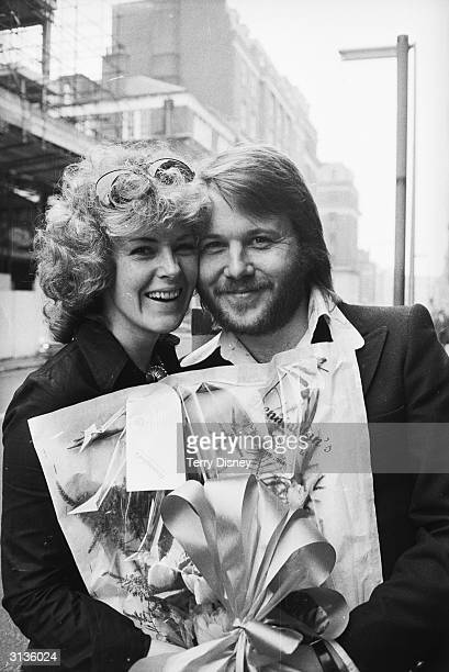 AnniFrid Lyngstad and Benny Andersson of the Swedish pop group ABBA carrying a bouquet