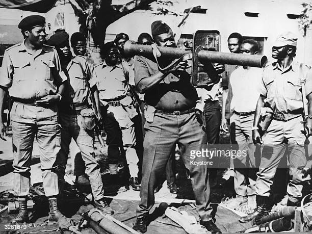 Idi Amin, Ugandan soldier, dictator and head of state, , firing a rocket launcher with troops still loyal to him.