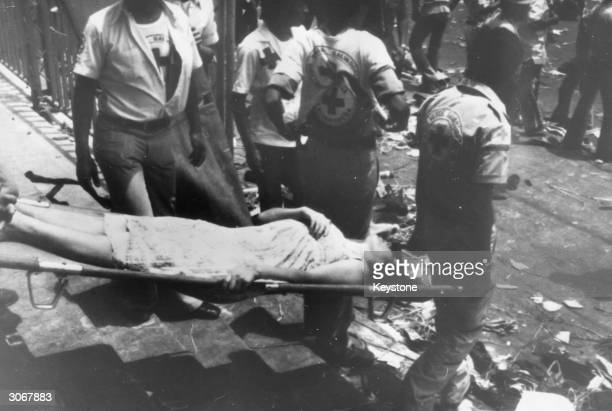 A woman being carried away on a stretcher after rioting and killing at the funeral of murdered Archbishop Oscar Romero in San Salvador