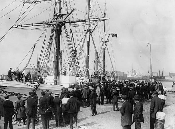 A crowd at Millwall Docks watches the departure of...