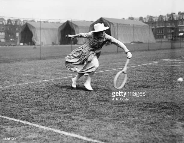 Left handed tennis player Miss May Turner goes for a low bounce at Queens Club, London.