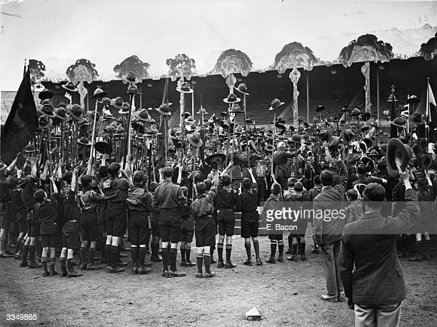A crowd of Boy Scouts raising their hats on sticks while cheering Prince Arthur Duke of Connaught and Sir Robert BadenPowell at the opening of the...