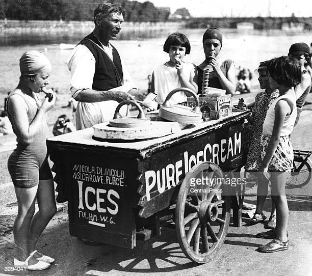 An ice cream seller sells ices to children by the Thames at Putney London