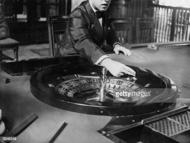 A croupier at a casino in Monte Carlo poised to spin the ball on a roulette wheel to start play