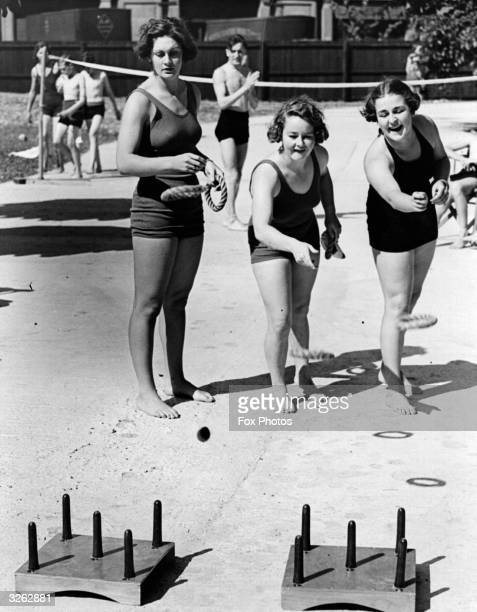 Australian swimming athletes playing a game of deck quoits on the sun terrace at the New Empire pool Wembley where the British Empire Games start on...
