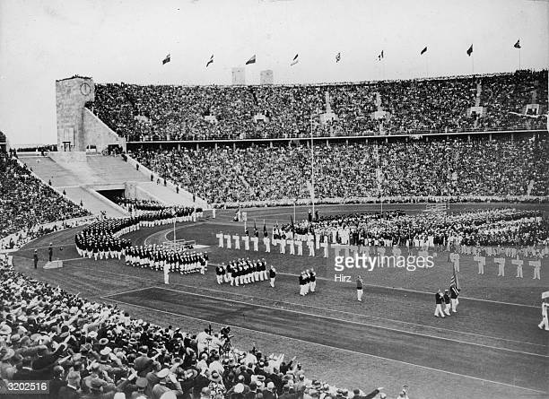 Fulllength image of athletes wearing dark blazers with either white trousers or white skirts entering the stadium during the opening ceremonies of...