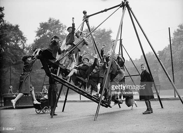 London children have fun on the swings at the new playground on the site of the Old Foundling Hospital in Bloomsbury