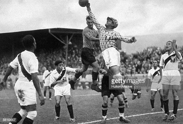 The gaily attired Peruvian goalkeeper leaps to make a save as Peru take on Austria in the Olympic games football tournament