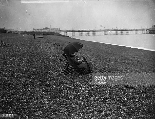 Two lone figures shelter under an umbrella on Brighton's pebbly beach and use another umbrella to cover their legs as they brave the grey weather