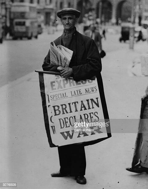 A newspaper seller carries a hoarding pronouncing the declaration of war between Britain and Germany on the Strand heading towards Admiralty Arch in...