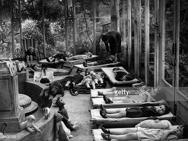 Evacuees from London resting on camp beds inside the conservatory of a large country house in Cheltenham during the Second World War