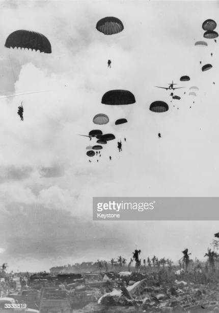 American paratroopers floating down onto a beachhead in support of Allied landings off the north coast of New Guinea during World War II.