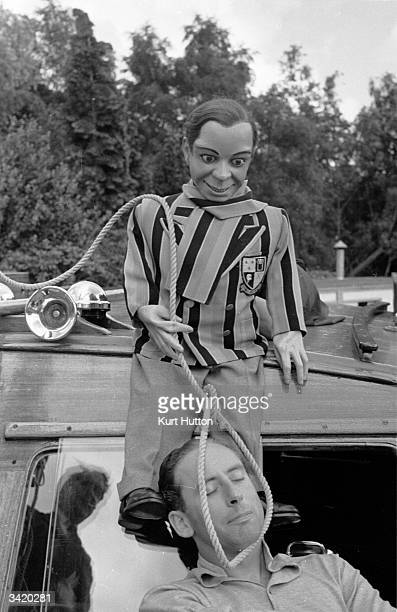Peter Brough's ventriloquist's dummy schoolboy Archie Andrews attempting to put a noose around his owner's neck during their holiday in Yarmouth...