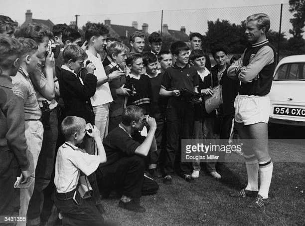 West Ham and England captain Bobby Moore being photographed by young fans during a break in a training session