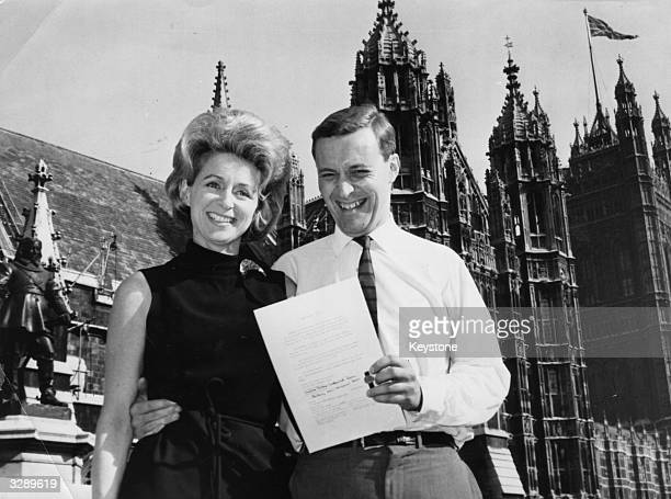 English Labour politician Anthony Wedgwood Benn and his wife educator and writer Caroline outside the Houses of Parliament London with the Instrument...