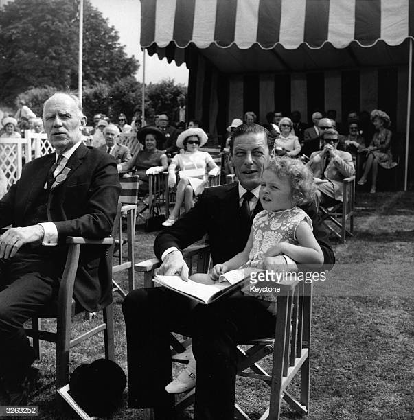 Angus Ogilvy husband of Princess Alexandra at a horse show with his young daughter Marina on his knee