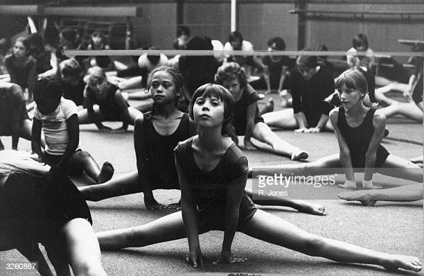 A gymnasium full of young girls taking their lesson in gymnastics very seriously