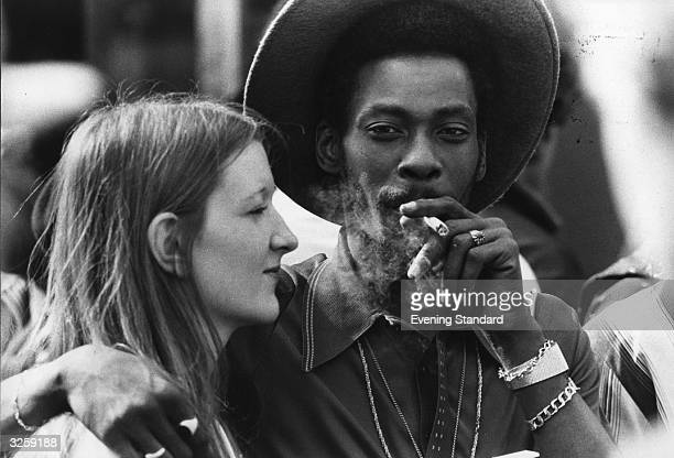 A young couple share a marijuana reefer at Notting Hill Carnival west London