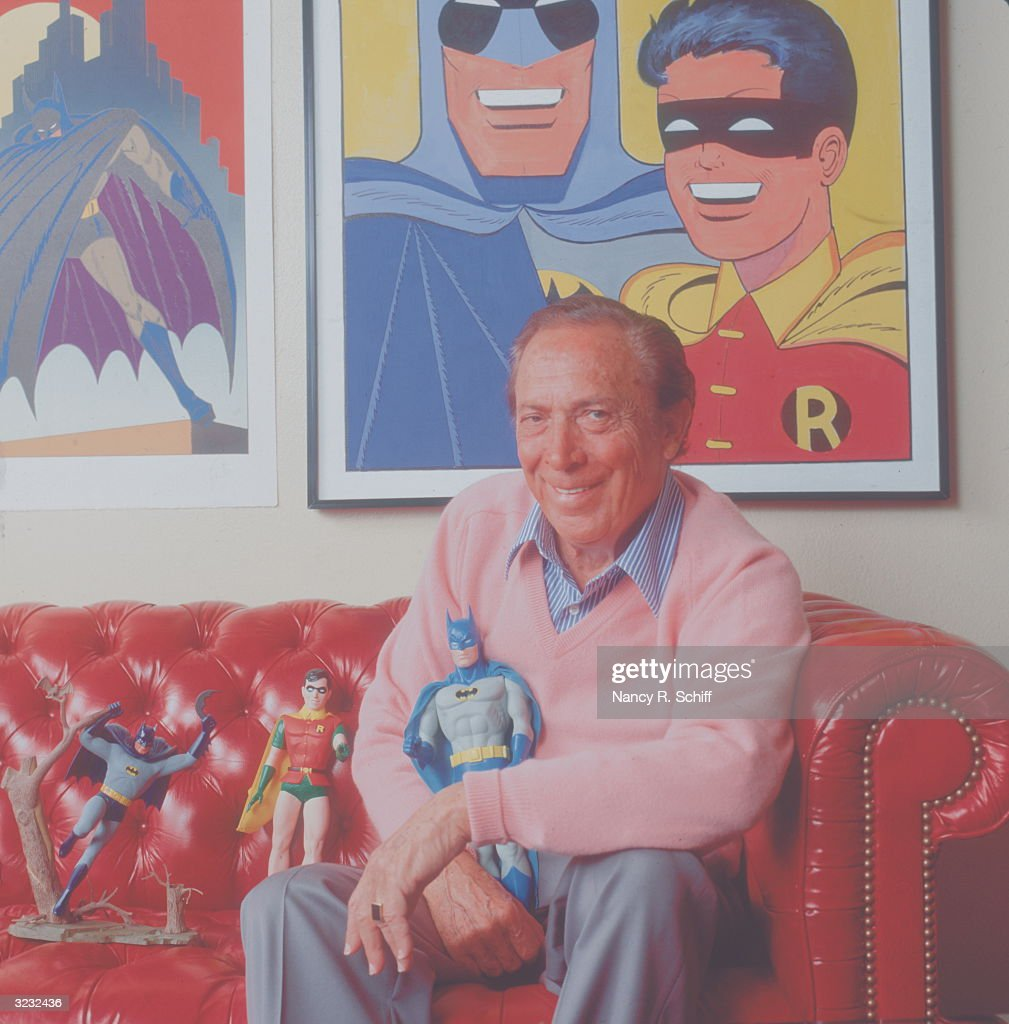American cartoonist Bob Kane, originator of Batman, sits on a couch in his apartment surrounded by Batman collectibles, including posters and action figures, to promote the release of the first Batman movie, Hollywood California.