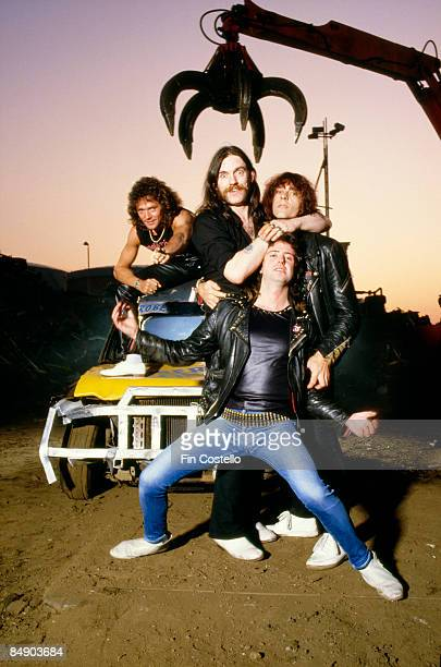 Photo of MOTORHEAD and LEMMY Posed group portrait LR Pete Gill Lemmy Phil Campbell and Mick 'Wurzel' Burston at a scrap yard in Pimlico London in...