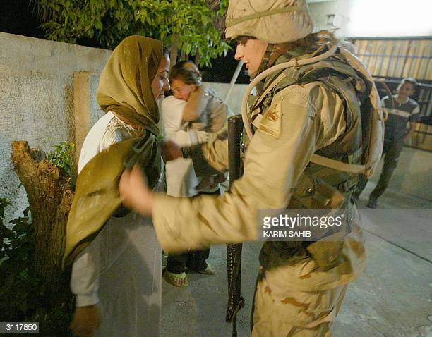 US 1st Cavalry female soldier searches an Iraqi woman outside her home during a housetohouse search operation in Baghdad's alJihad quarter early 21...