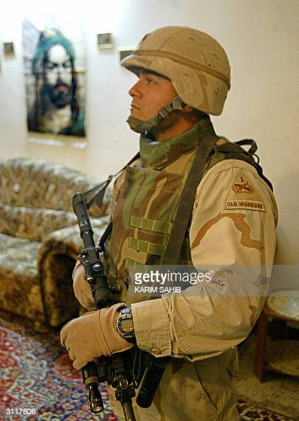 US 1st Cavalry soldier stands on guard with a portrait of Prophet Mohammed's cousin and soninlaw Imam Ali in the background as his comrades search a...