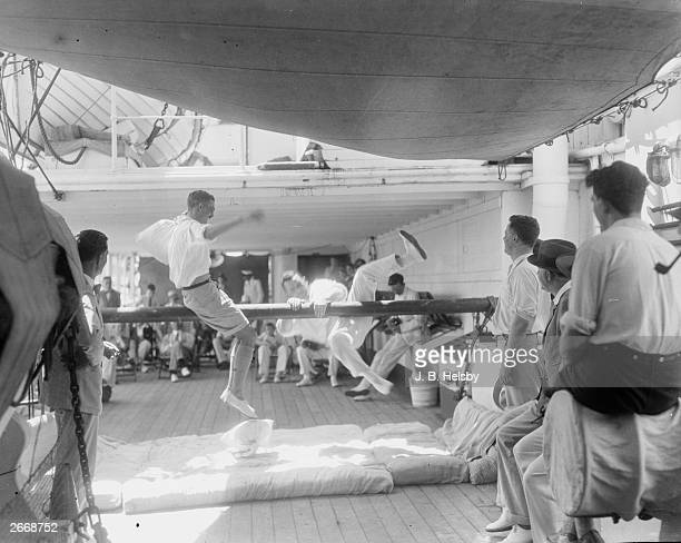 1st class passengers on the Union Castle liner Durham Castle try to knock each other off the bolster bar onto a pile of mattresses