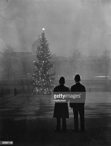 Two policemen regard London's 64ft Christmas tree a gift from Norway illuminated in Trafalgar Square in front of the National Gallery